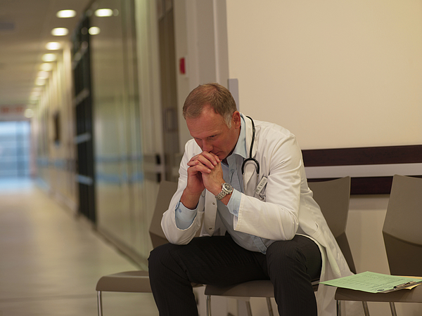 Frustrated doctor sitting in hospital waiting area Photograph by Chris Ryan