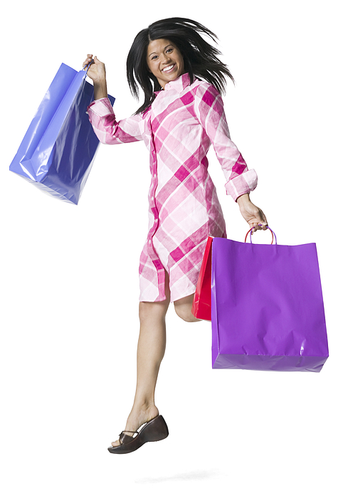 Full Body Portrait Of A Young Adult Female In A Pink Patterned Dress As She Jumps With Shopping Bags Photograph by Photodisc