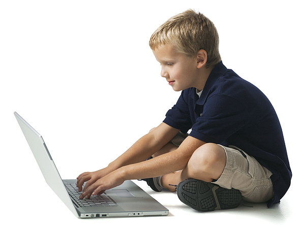 Full Body Shot Of A Young Male Child As He Sits And Works On A Laptop Computer Photograph by Photodisc
