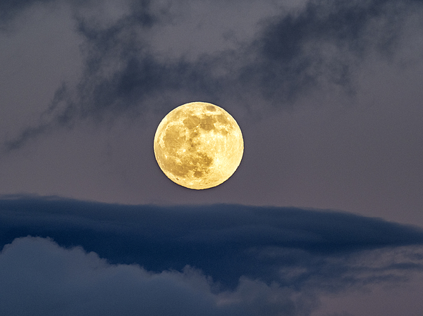 Full frame of the full moon at sunset with a sky with clouds. Photograph by Jose A. Bernat Bacete