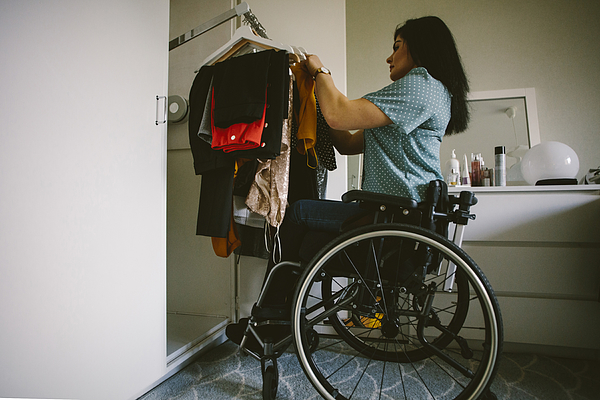 Full length side view of young disabled woman looking at clothes hanging in wardrobe Photograph by Maskot