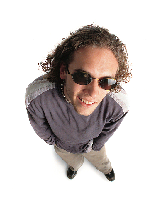 Funky Caucasian Male With Curly Brown Hair Wearing Alternative Style Clothing And Sunglasses Looks Up And Smiles Photograph by Photodisc