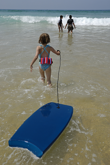 Girl (5-7) walking into surf, pulling float, rear view Photograph by Sami Sarkis