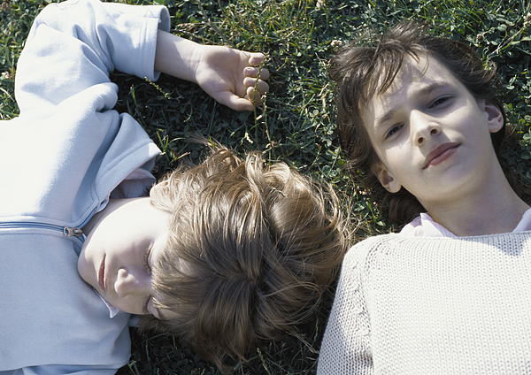 Girl And Boy Lying On Grass Photograph by Laurence Mouton
