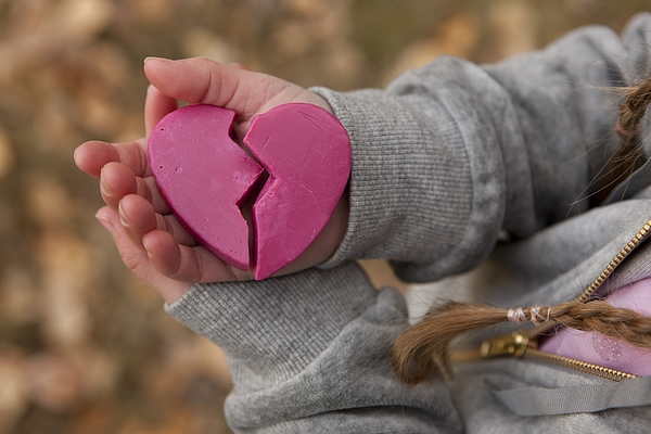 Girl holding broken heart Photograph by Design Pics/Ron Nickel