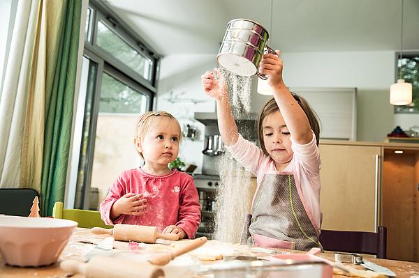 Girl sieving flour in kitchen Photograph by Nils Hendrik Mueller
