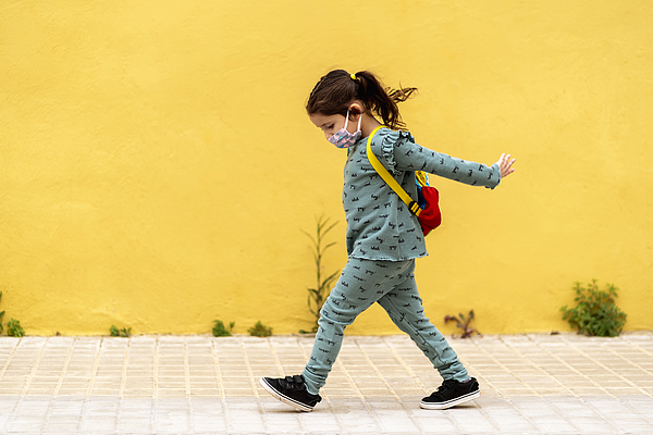 Girl Walking With Backpack And Mask Outdoors Photograph by Westend61
