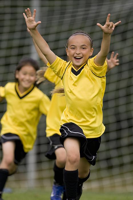 Girls (8-13) playing football, laughing Photograph by John Giustina