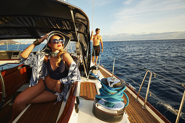 Glamorous woman relaxing on yacht deck Photograph by Colin Anderson Productions pty ltd