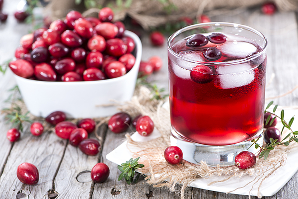 Glass of fresh cranberry juice and a bowl of cranberries Photograph by HandmadePictures