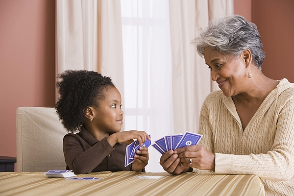 Grandmother and granddaughter playing cards Photograph by Jupiterimages