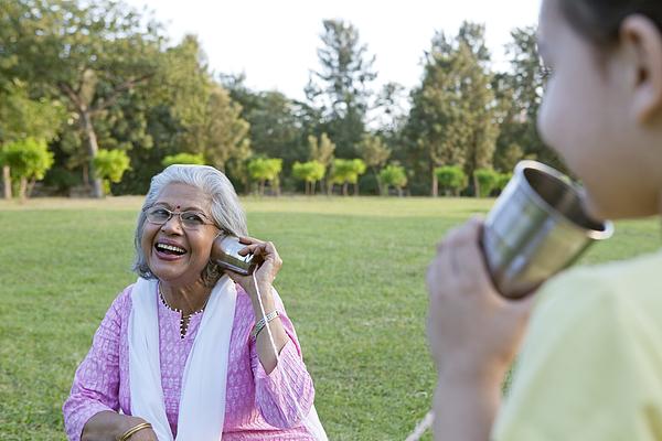 Grandmother and granddaughter talking through tin cans Photograph by Ravi Ranjan
