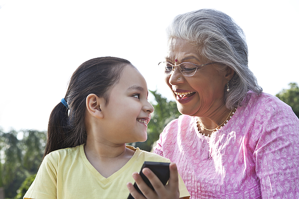 Grandmother and granddaughter with a mobile phone Photograph by Ravi Ranjan