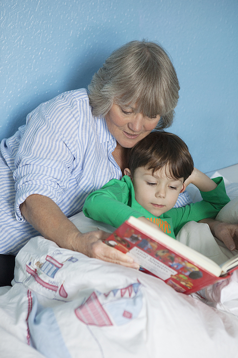 Grandmother and grandson reading book in bed Photograph by Compassionate Eye Foundation/Natasha Alipour Faridani