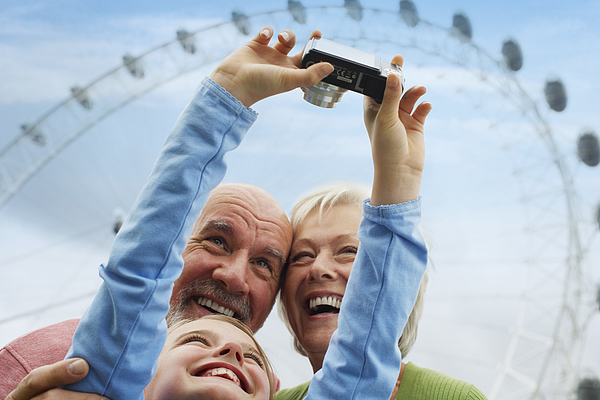 Grandparents and Granddaughter with Digital Camera Photograph by Fuse