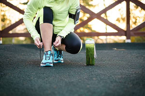 Green Detox Smoothie Cup And Woman Lacing Running Shoes Before Workout. Photograph by Lifemoment