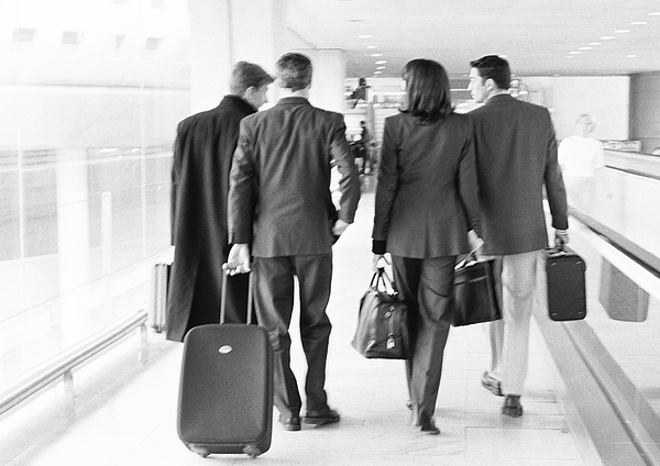 Group of business people walking through terminal, full length, rear view, b&w. Photograph by Teo Lannie