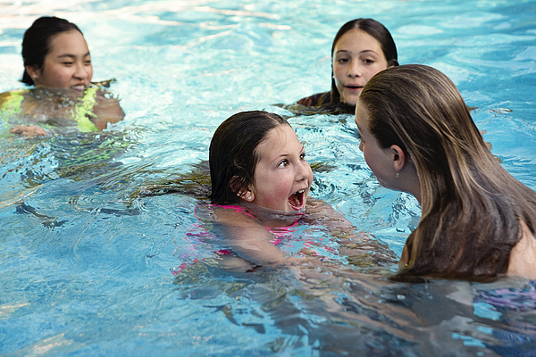 Group of preteen and teenage girls in pool. Photograph by Martinedoucet