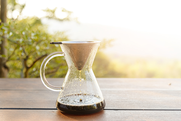 Hand drip coffee making pour over coffee with hot water being poured from a kettle with mountain view and natural green view feeling chill and relax in nature Photograph by Pratchaya