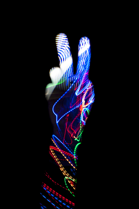 Hand With Light Trail Making V For Victory Sign Photograph by Colormos