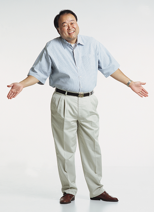 Handsome Middle Aged Asian Adult Male Wearing A Light Blue Short Sleeved Shirt And Cream Colored Slacks Stands With Shrugged Shoulders And Hands In The Air As He Looks At The Camera With A Anxious Smile Photograph by Photodisc