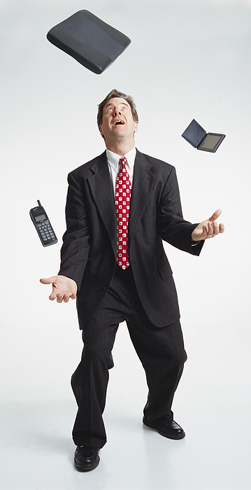 Handsome Middle Aged Caucasian Businessman Dark Suit Juggles Laptop Computer Palm Pilot Cell Phone Photograph by Photodisc