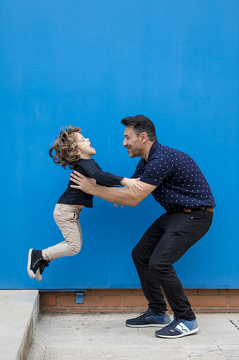 Happy father playing with son at blue wall Photograph by Westend61