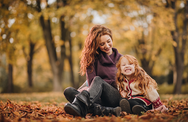 Happy redhead mother and daughter relaxing in the park. Photograph by Skynesher