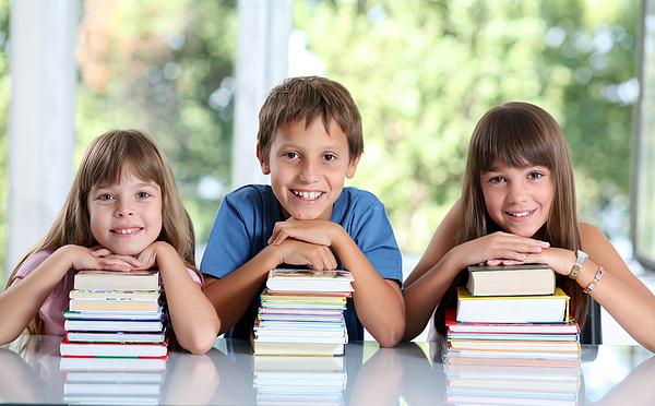 Happy schoolchildren with many books. Photograph by Skynesher