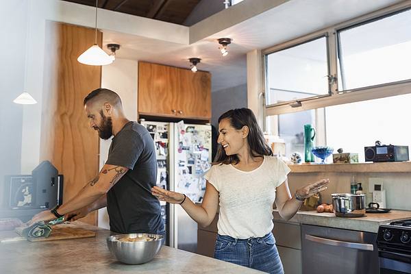 Happy woman gesturing while talking to man cutting vegetables in kitchen Photograph by Maskot