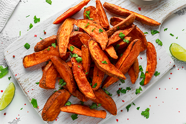 Healthy Homemade Baked Orange Sweet Potato wedges with fresh cream dip sauce, herbs, salt and pepper Photograph by DronG