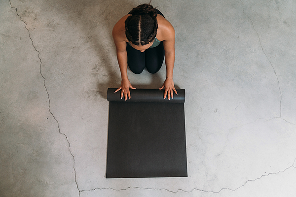 High angle view of a young adult woman closing a yoga mat Photograph by FilippoBacci