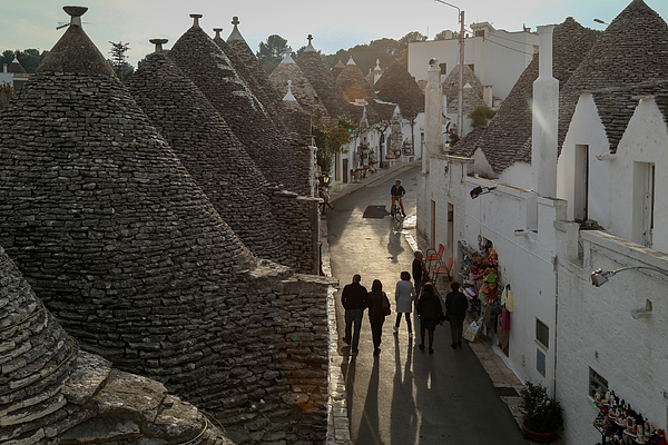 High Angle View Of People Walking On Street Amidst Trullo Houses With Conical Roofs In Alberobello Photograph by Alessandro Miccoli / EyeEm
