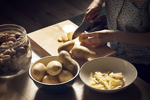High angle view of woman cutting potatoes on cutting board at home Photograph by Cavan Images