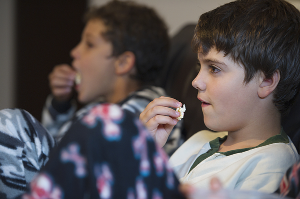 Hispanic boys eating popcorn and watching television Photograph by GM Visuals