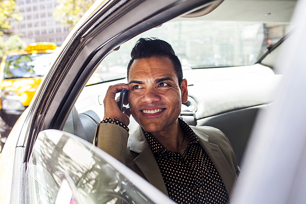 Hispanic businessman talking on cell phone in back seat of car Photograph by Adam Hester