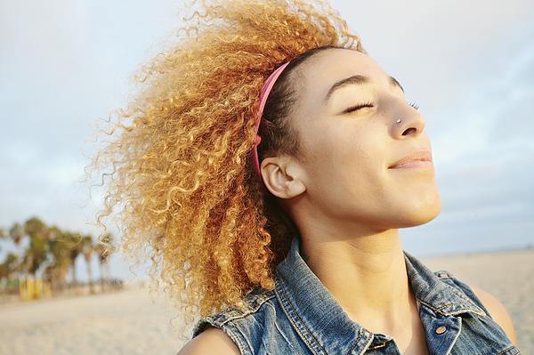 Hispanic woman smiling at beach Photograph by Peathegee Inc