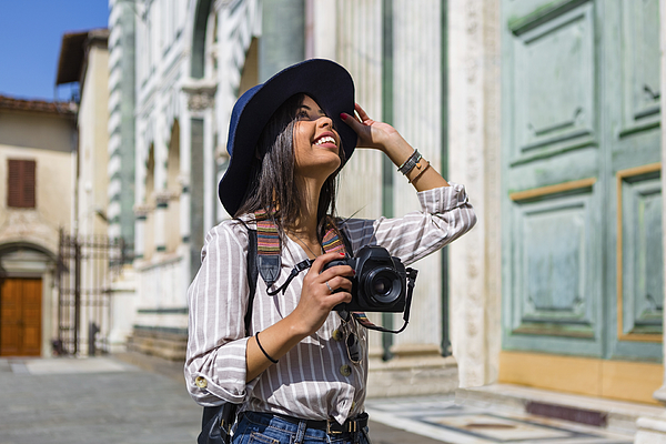 Italy, Florence, happy young tourist with camera looking up Photograph by Westend61
