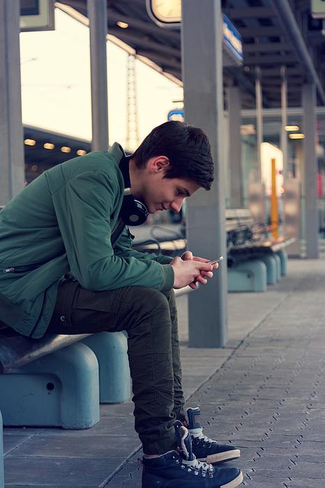 Jugendlicher hört Musik und wartet auf dem Zug Photograph by Lucaa15