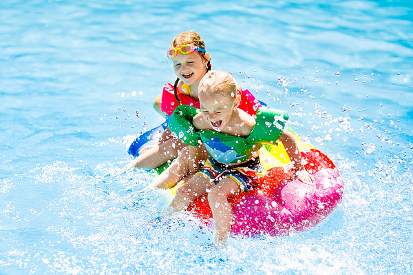 Kids on inflatable float in swimming pool. Photograph by FamVeld