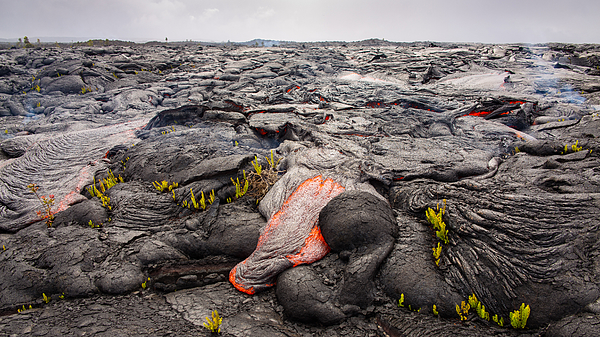 Lava destroys a landscape under cloudy skies Photograph by Tyler Hulett