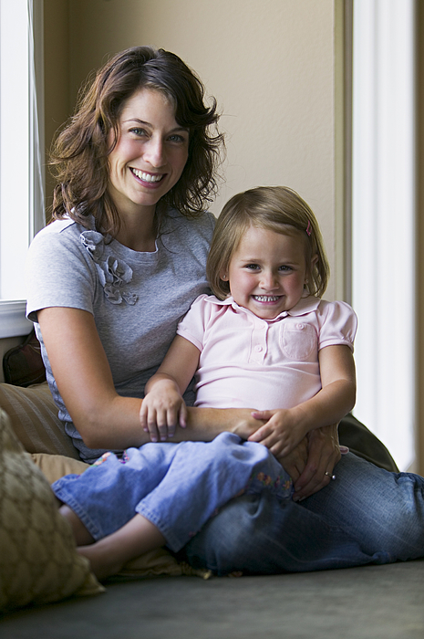 Lifestyle Portrait Of A Mother As She Sits On A Couch And Holds Her Young Daughter Photograph by Photodisc