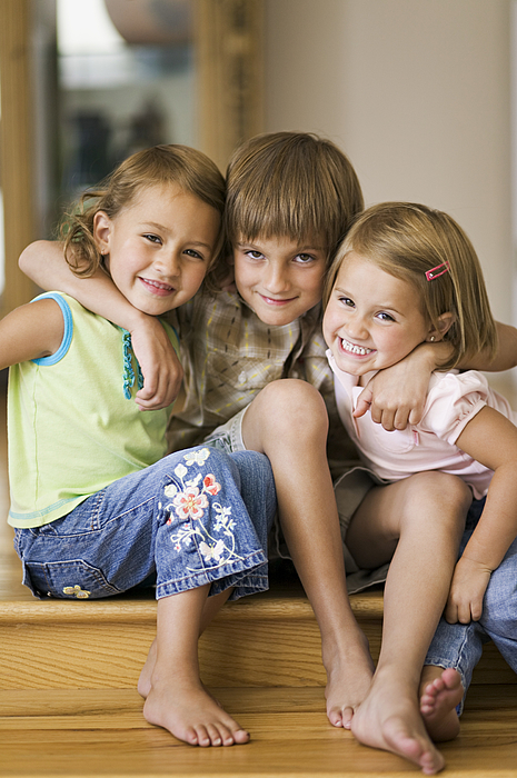 Lifestyle Portrait Of Three Siblings As They Put Their Arms Around Each Other And Smile Photograph by Digital Vision