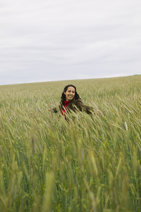 Lifestyle Shot Of A Young Adult Woman As She Walks Through Tall Green Grass Photograph by Photodisc