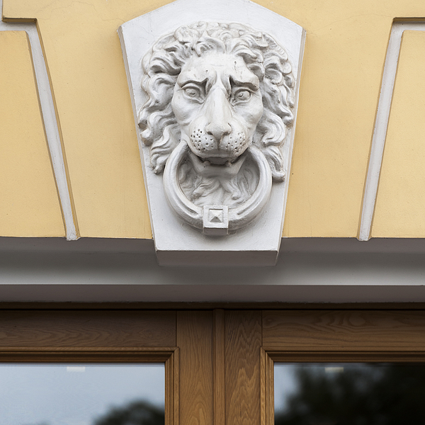 Lions face statue carved on the wall of a building Photograph by Fotosearch