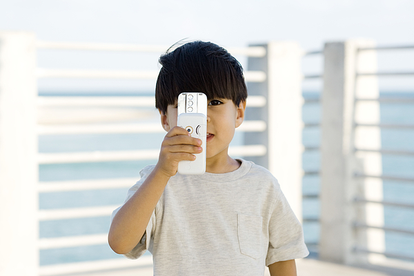 Little boy holding slide camera phone in front of face, looking at camera Photograph by PhotoAlto/Frederic Cirou