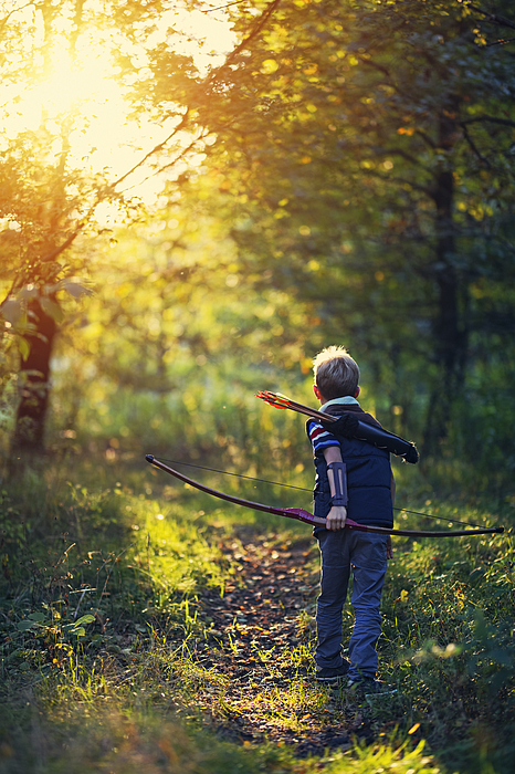 Little boy playing with bow in forest Photograph by Imgorthand
