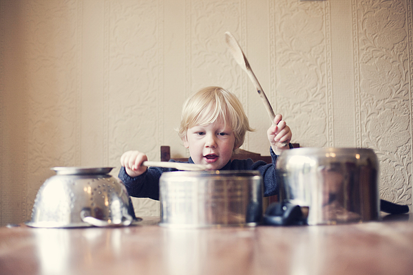 Little boy using saucepans as drums Photograph by Sally Anscombe