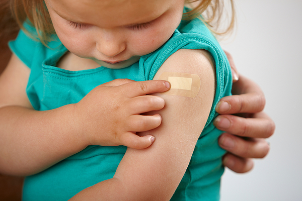 Little girl looking at plaster where she has had an injection Photograph by Image Source