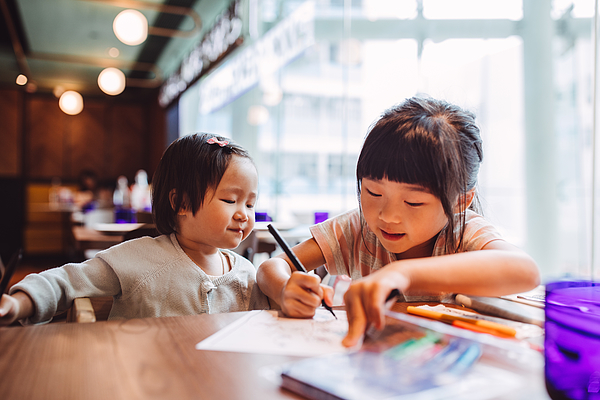 Little girl teaching her little toddler sister to draw joyfully in a restaurant. Photograph by Images By Tang Ming Tung